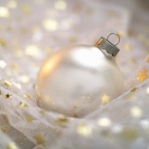 Silvery-white bauble nestled on white net fabric scattered gold stars and glitter